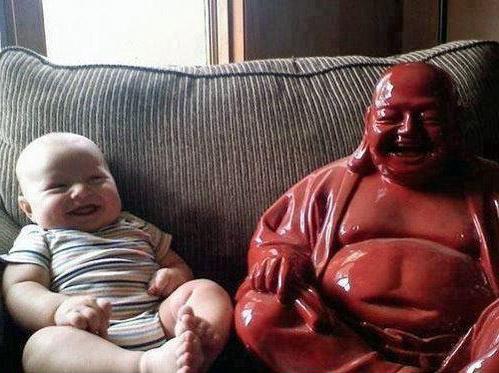 Ein Baby sitzt lachend neben einer Buddha-Statue auf einem Sofa. Die beiden sehen sich sehr ähnlich.