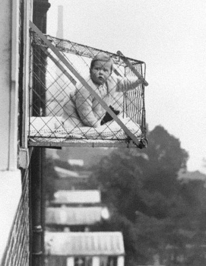 Ein Baby sitzt um 1920 in einem Käfig, der an einem Hochhaus an der Außenwand angebracht ist.