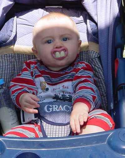 Ein Baby mit einem Schnuller, der aussieht wie zwei schrecklicke Zähne.