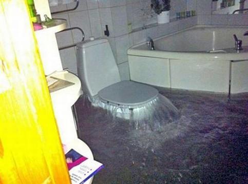 Aus einem WC in einem Badezimmer sprudelt Wasser hervor und setzt das komplette Badezimmer unter Wasser.