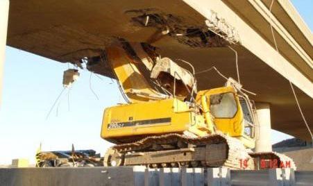 Ein Bagger zerstört eine Brücke.