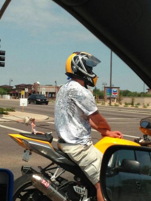 Ein Motorradfahrer hat auf seinem Sozius eine Barbiepuppe sitzen.