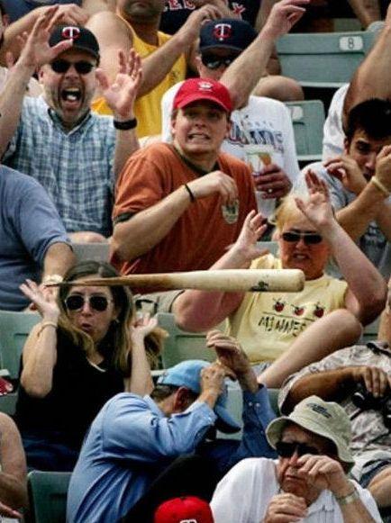 Ein Baseballschläger fliegt auf eine Gruppe Zuschauer in einem Stadion zu, diese schauen sehr erschrocken aus.