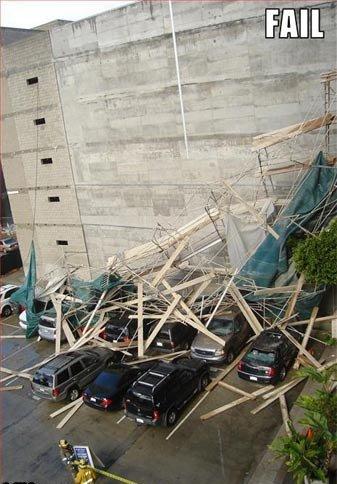 Ein großes Baugerüst ist eingestürzt und hat eine Reihe parkender Autos unter sich begraben.