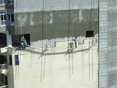 Männer bauen ein Haus mit einem Baugerüst, das nur aus Brettern und Seilen besteht.