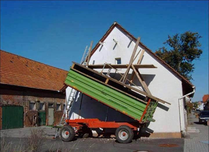 Ein Baugerüst für ein Haus wurde selber gebaut, indem eine schräge Holzkonstruktion auf einen gekippten Anhänger montiert wurde. Es sieht recht gefährlich aus.
