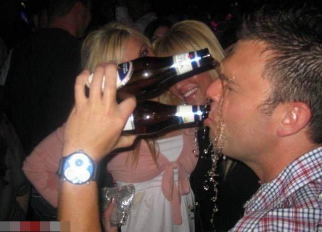 Ein Mann hat zwei Bierflaschen in einer Hand und versucht so zu trinken. Mit der oberen Flasche kippt er sich das Bier ins Gesicht.
