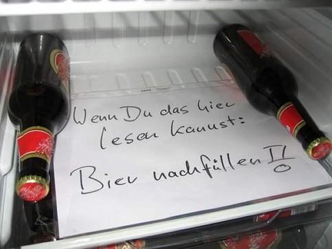 """Ein Kühlschrank, auf dessen Boden zwischen zwei Bierflaschen ein Zettel zu lesen ist: """"Wenn Du das hier lesen kannst: Bier nachfüllen!"""""""