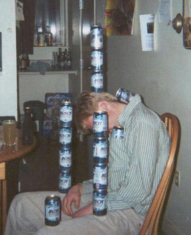 Ein Mann ist scheinbar betrunken eingeschlafen. Andere haben lauter Bierdosen auf ihm gestapelt.