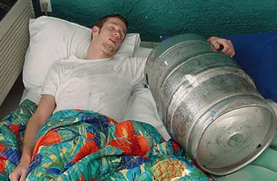 Ein Mann liegt in einem Bett mit einem Bierfaß und hält dieses im Arm.