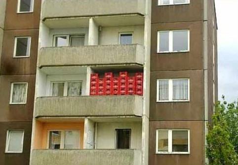 Auf einem Balkon stehen viele Bier-Kisten.
