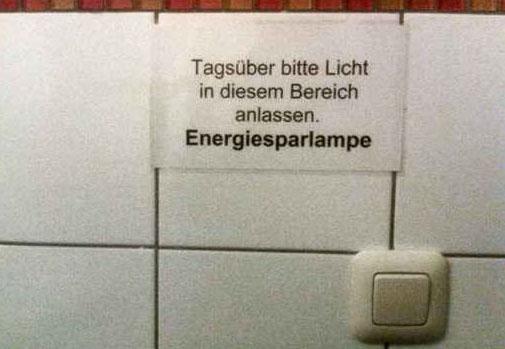 """Über einem Lichtschalter hängt ein Zettel: """"Tagsüber bitte Licht in diesem Bereich anlassen. Energiesparlampe""""."""