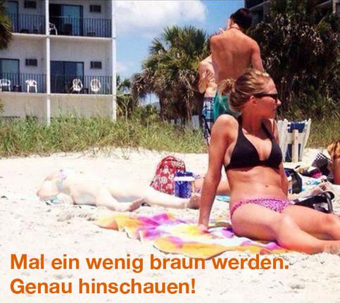 Ein Foto von einem Strand. Wenn man genau hinschaut, entdeckt man auf einem Handtuch eine Frau. Sie hat fast dieselbe Farbe wie der Sand.