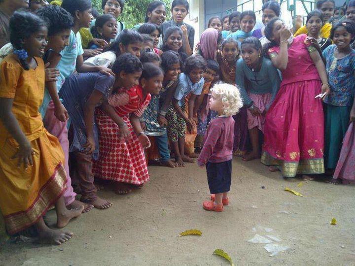 Ein blonder und gelockter Junge wird von vielen Indern staunend beobachtet.
