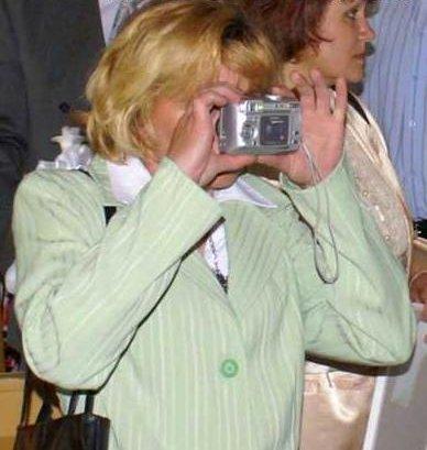 Ein Blondine hält einen Fotoaparat falsch herum und schaut in die Linse.