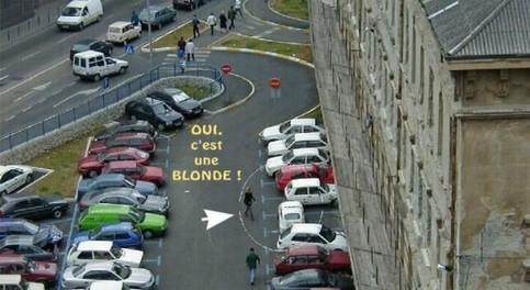Ein Parkplatz, auf dem ein Auto quer in einer Parklücke steht und aus dem eine Blondine aussteigt.