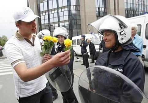 Ein Mann überreicht einer Polizistin in Schutzmontur eine Blume.