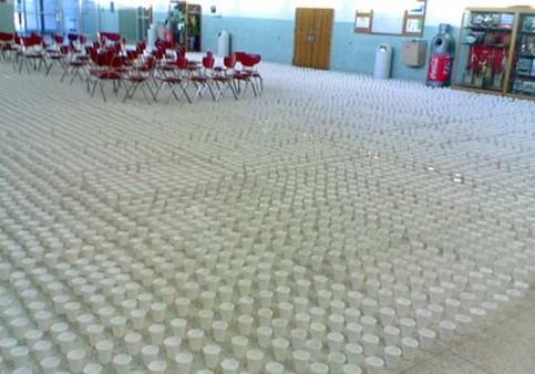 In einem Raum, wahrscheinlich ein Saal einer Schule, ist der komplette Boden mit Bechern vollgestellt.