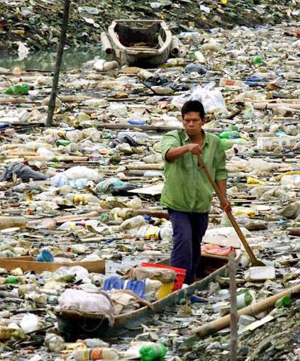 Ein Mann paddelt mit einem Boot durch einen See voller Müll.