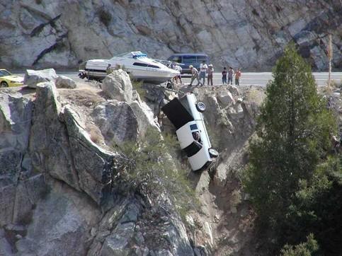 Ein Auto ist einen Abhang hinunter gestürzt und wird dabei nur von einem angehängten Boot gehalten.