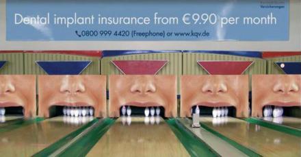 Auf einer Bowlingbahn sehen die Kegel aus wie Zähne in einem Mund.