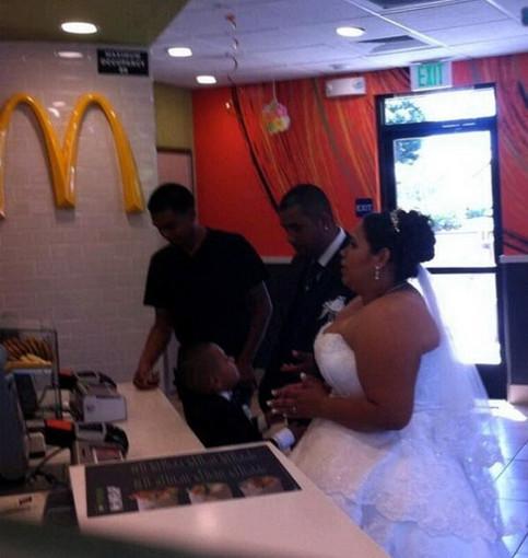 Ein Brautpaar mit Anzug und Brautkleid steht in der Schlange bei McDonalds an.