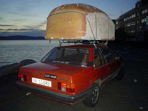 Ein Auto mit einem gigantischen Brot auf dem Dachgepäckträger.