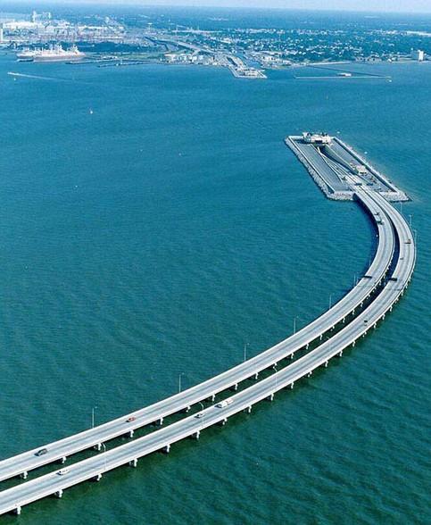 Eine Brücke im Wasser, die zu einem Tunnel wird.