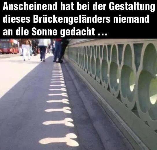 Durch ein Brückengeländer scheint die Sonne. Der Schatten der dadurch auf den Bürgersteig geworfen wird, sieht aus wie ein Penis.
