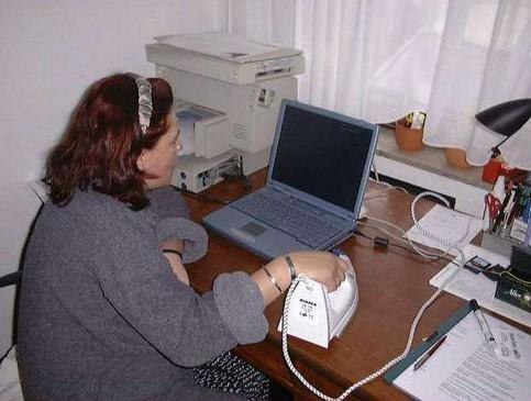 Eine Frau sitzt vor einem Computer und verwendet statt einer Maus ein Bügeleisen.