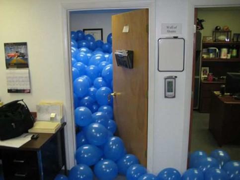 In einem Büro wurde ein Zimmer komplett mit blauen Luftballons gefüllt.
