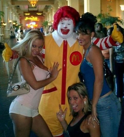 Drei Frauen schmiegen sich begeistern an das Maskottchen einer Fast-Food-Kette.