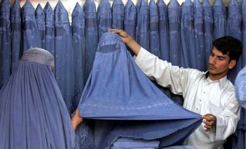 Eine Frau wird in einem Laden beim Kauf einer Burka beraten.