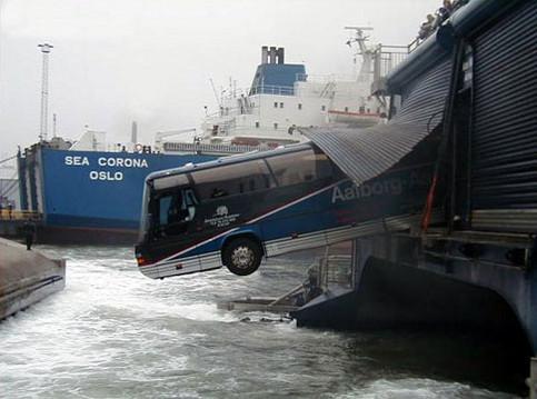 Ein Bus ist durch eine Wand gefahren und hängt halb über dem Wasser im Hafen.