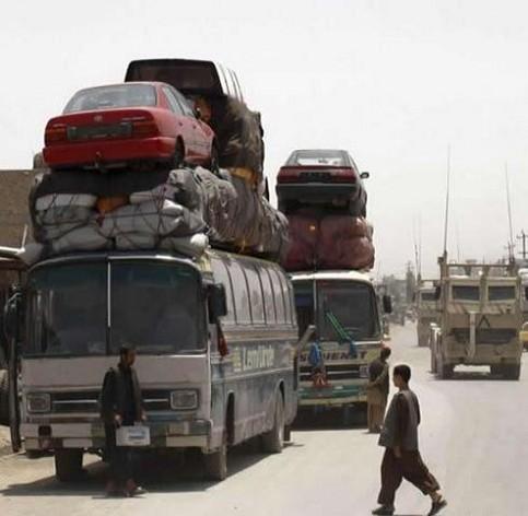 Buse sind voll beladen und transportieren unter anderem Autos auf dem Dach.