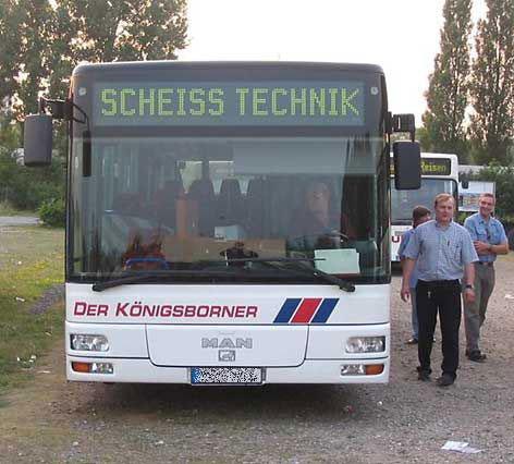 """Ein Bus mit der Einblendung """"SCHEISS TECHNIK""""."""