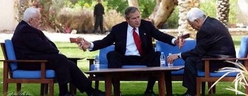 George W. Bush reicht Ariel Sharon und Machmud Abbas Pistolen.