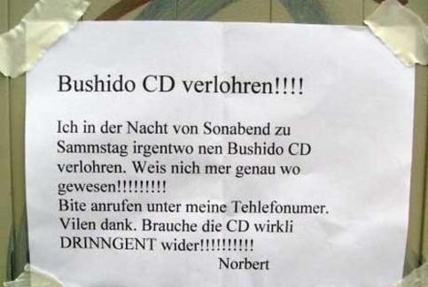 Norbert sucht auf einem Aushang mit haarsträubenden Rechtschreibfehlern nach seiner Bushido-CD.