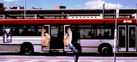 Auf den Türen eines Busses sind ein Mann und eine Frau abgebildet, die sich beim Schließen der Türen küssen.
