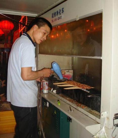 Ein chinesischer Mann bereitet eine Pizza in einem Imbiss mit einem Fön zu.