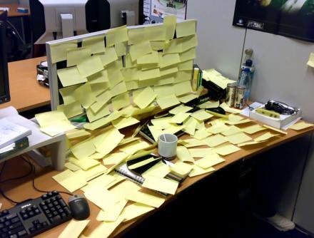 Ein Arbeitsplatz ist völlig mit gelben PostIt-Notizzetteln beklebt.