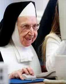 Eine Nonne sitzt mit begeistertem Gesichtsausdruck vor einem Computer und klickt eine Maus.