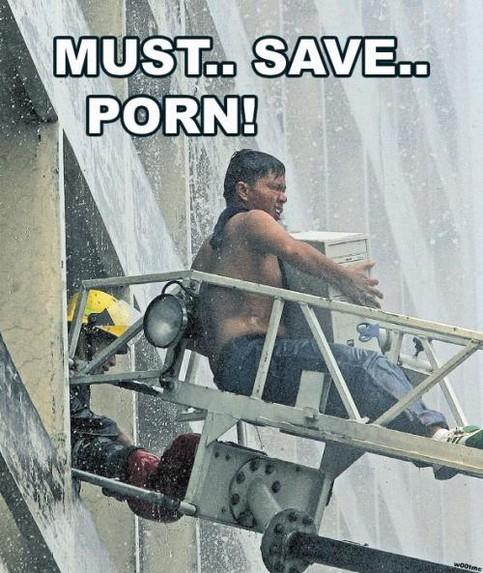 Ein Mann wird von der Feuerwehr mit einer Leiter aus einem Haus gerettet, er hat seinen Computer dabei.