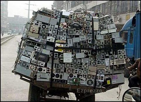 Ein Laster hat unglaublich viele Netzteile und Computer geladen und diese mit Bändern befestigt.