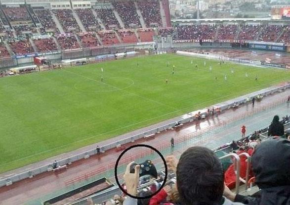 Ein Zuschauer bei einem Fußballspiel hält einen Konsolen-Controller in der Hand, als würde er die Spieler fernsteuern.