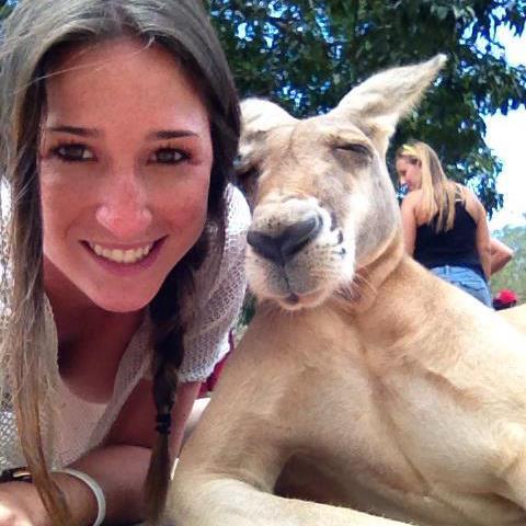 Auf einem Foto lehnt sich ein Känguru ganz lässig an eine junge Frau und schaut sehr cool aus.