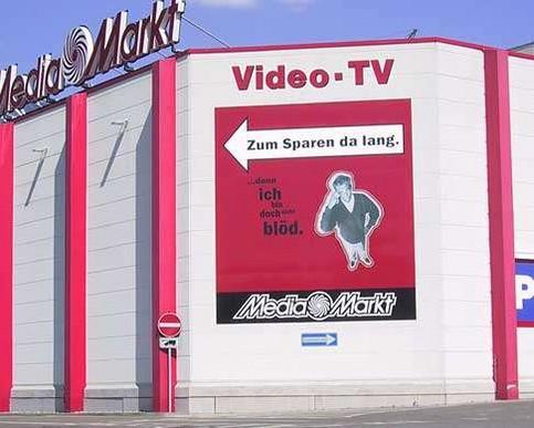 """Eine Werbung zeigt mit einem Pfeil """"Zum Sparen da lang"""", dort ist jedoch eine Einbahnstraße in die andere Richtung."""