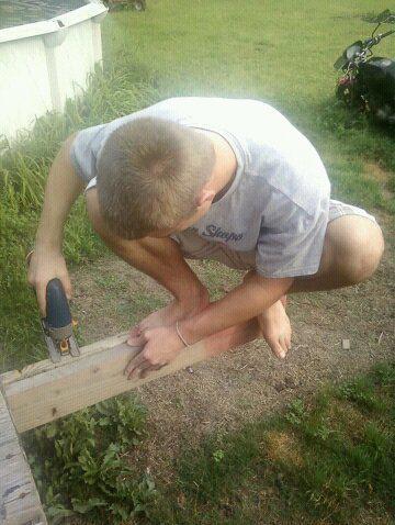 Ein Mann hockt auf einem Balken, den er gleichzeitig mit einer Säge absägt.