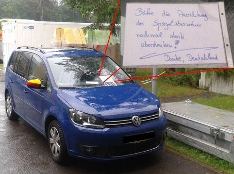 """An einem Auto sind die Deutschland-Rückspiegelüberzieher falsch herum aufgezogen. Daher hat jemand einen Zettel hinter die Scheibenwischer geklemmt: """"Bitte die Ausrichtung der Spiegelüberzieher nochmal stark überdenken! Danke, Deutschland"""""""