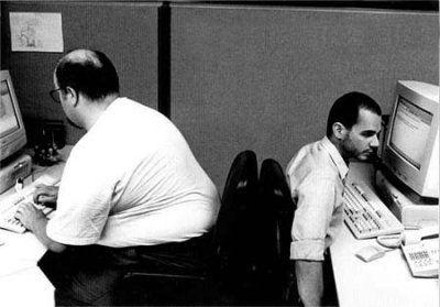 Ein dicker und ein dünner Kollege sitzen auf ihren Stühlen so zusammen, dass der Dünne zusammengedrückt wird.